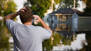 man-surveying-flood-damage-300x169